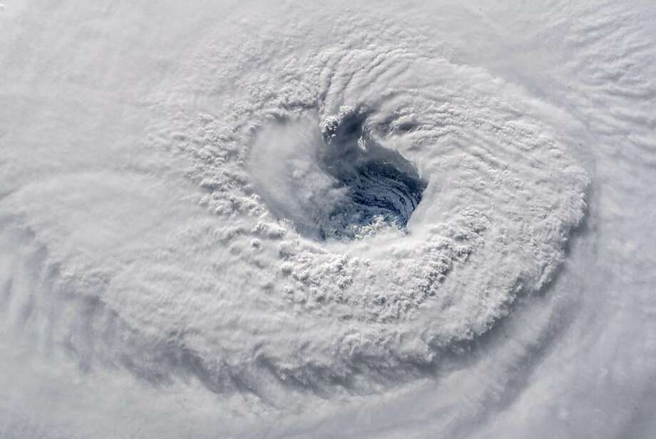 "A high definition camera outside the International Space Station captured a NASA view of the eye of Hurricane Florence at 7:50 a.m. EDT on September 12, 2018, shown in this video still  taken as Florence churned across the Atlantic in a west-northwesterly direction with winds of 130 miles an hour. - Powerful Hurricane Florence headed toward the US East Coast Tuesday, prompting authorities to order more than a million people to evacuate the path of the extremely dangerous storm forecasters said could soon intensify. Residents scrambled to flee as the menacing Category 4 storm packing winds of 140 miles (220 kilometers) per hour moved closer.""This is one of the worst storms to hit the East Coast in many years,"" President Donald Trump warned on Twitter. ""Please be prepared, be careful and be SAFE!""  Photo: HO, AFP/Getty Images"