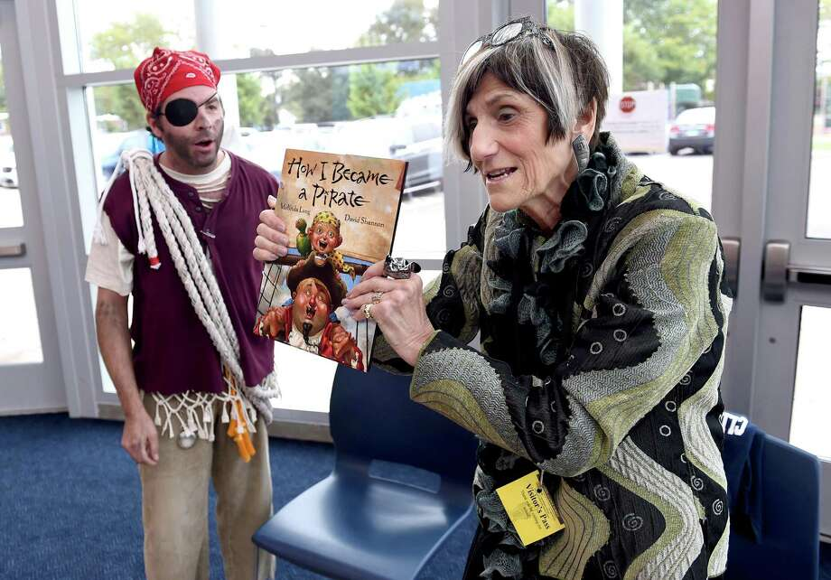 """U.S. Rep. Rosa L. DeLauro, right, receives the book, """"How I Became a Pirate,"""" from senior staffer Lou Mangini dressed as Landlubber Lou to read to first-graders at Clinton Avenue School in New Haven Wednesday. Photo: Arnold Gold / Hearst Connecticut Media / New Haven Register"""