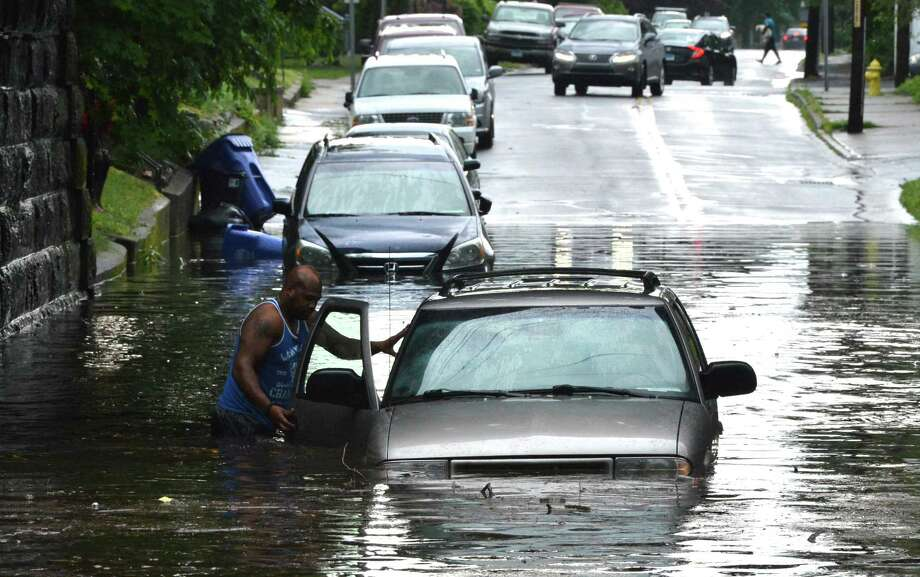 A good Samaritan checks inside of a pick up truck to see if there is someone inside after it failed to make it through fast rising high water under the Metro-North rail bridge on Osborne St. on Thursday June 28, 2018 in Norwalk Conn. A line of thunderstorms and heavy rain moved through the area flooding roads causing traffic jams everywhere Photo: Alex Von Kleydorff / Hearst Connecticut Media / Norwalk Hour