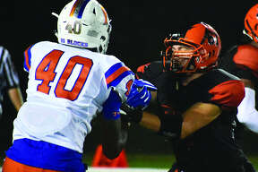 Edwardsville offensive lineman Joe Russo, right, blocks an East St. Louis pass rusher during Week 3 action inside the District 7 Sports Complex.