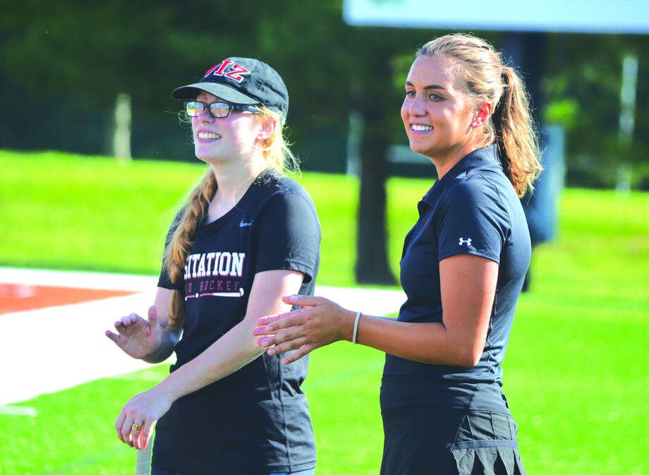 Visitation Academy field hockey coach Abby Urbanek, right, watches along with assistant coach Laura Eckelkamp during the pregame introductions before Monday's game at Edwardsville. Urbanek is a 2014 EHS graduate and graduated from Indiana University last spring. Photo: Scott Marion
