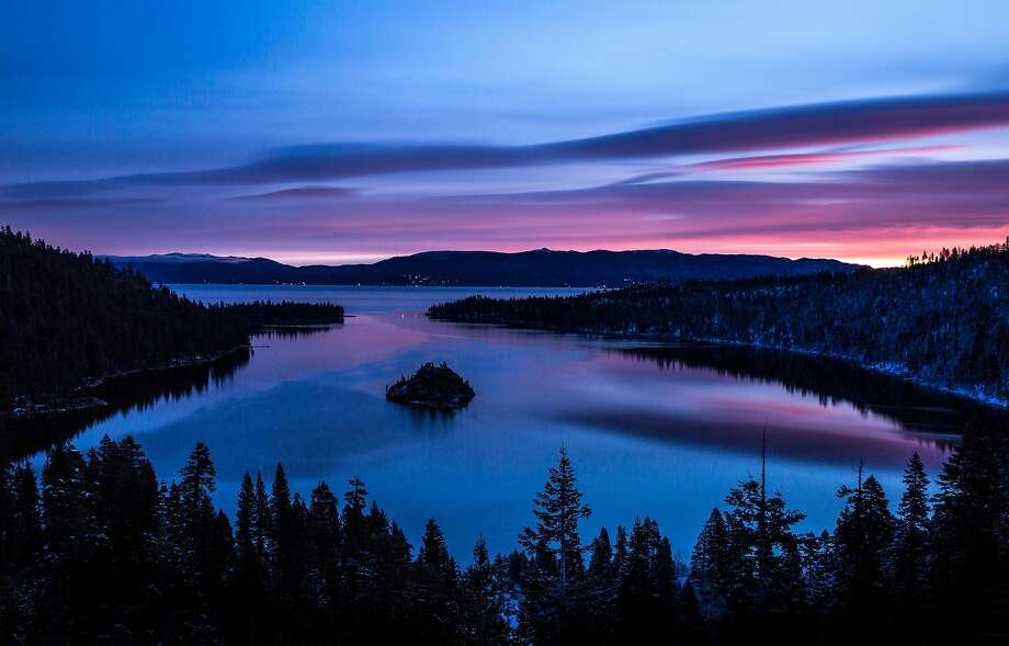 Sunrise colors the sky over Emerald Bay in South Lake Tahoe, where state park divers have found wreckages of two large barges and 12 recreational boats that sank as long ago as the 1920s. Photo: George Rose / Getty Images