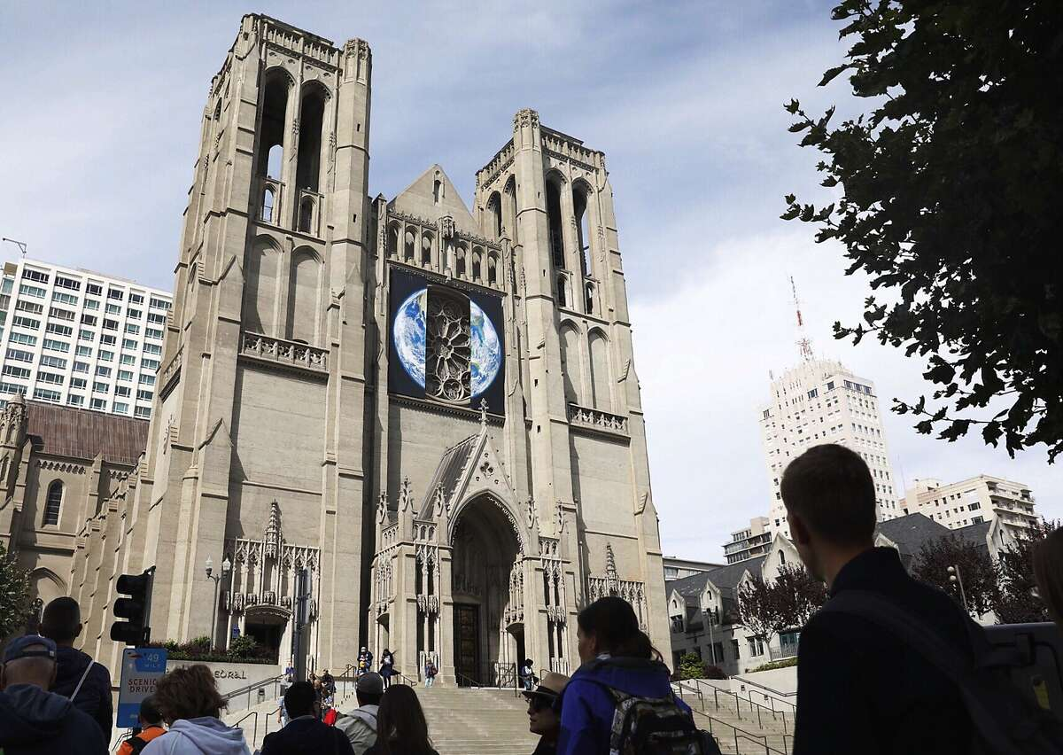 A group of tourists make their way up the steps of Grace Cathedral where an Earth banner is seen surrounding the main facade ahead of the Global Climate Action Summit in San Francisco, Calif. Wednesday, September 12, 2018.