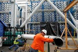 In this March 11, 2015 picture, workers move a pipe in front of the 2000 pressure vessels that will be used to convert seawater into fresh water through reverse osmosis in the western hemisphere's largest desalination plant Wednesday, March 11, 2015, in Carlsbad, Calif. Despite the San Diego region's costly investments to prepare for drought, the measures count for nothing under sweeping statewide cuts to urban water use approved this month. (AP Photo/Gregory Bull)