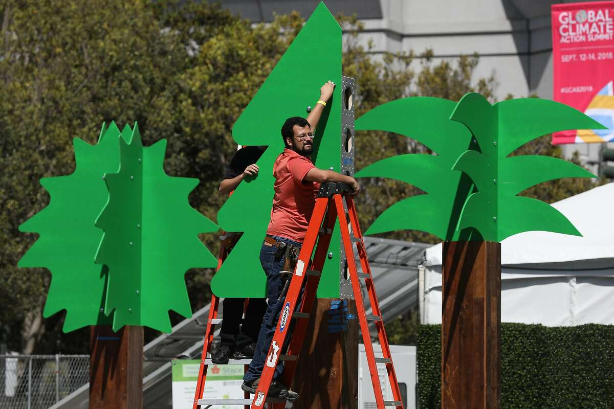 Derek Hercs (right) and Cody Bazurto (partially seen left), both with Local 16 International Alliance of Theatrical Stage Employees, work on Howard Street as they help set up for the Global Climate Action Summit at Moscone South on Wednesday, September 12, 2018 in San Francisco, Calif.