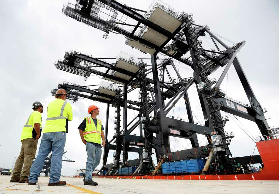 Workers pause to watch at the Port of Houston's Bayport Container Terminal as new super post-panamax cranes are delivered. The cranes recently completed a nearly 90-day journey from Shanghai to the container terminal in Seabrook. Photo: Karen Warren, Staff Photographer / © 2018 Houston Chronicle