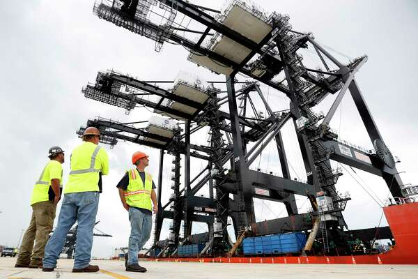 Workers pause to watch at the Port of Houston's Bayport Container Terminal as new super post-panamax cranes are delivered. The cranes recently completed a nearly 90-day journey from Shanghai to the container terminal in Seabrook.