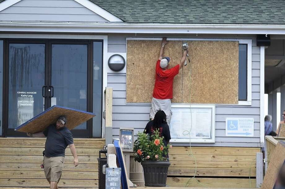 Crews board up the Oceanic restaurant in Wrightsville Beach, N.C. It is expected that the damage in the hurricane's path won't be quickly overcome. Photo: Matt Born / Wilmington (N.C.) Star-News