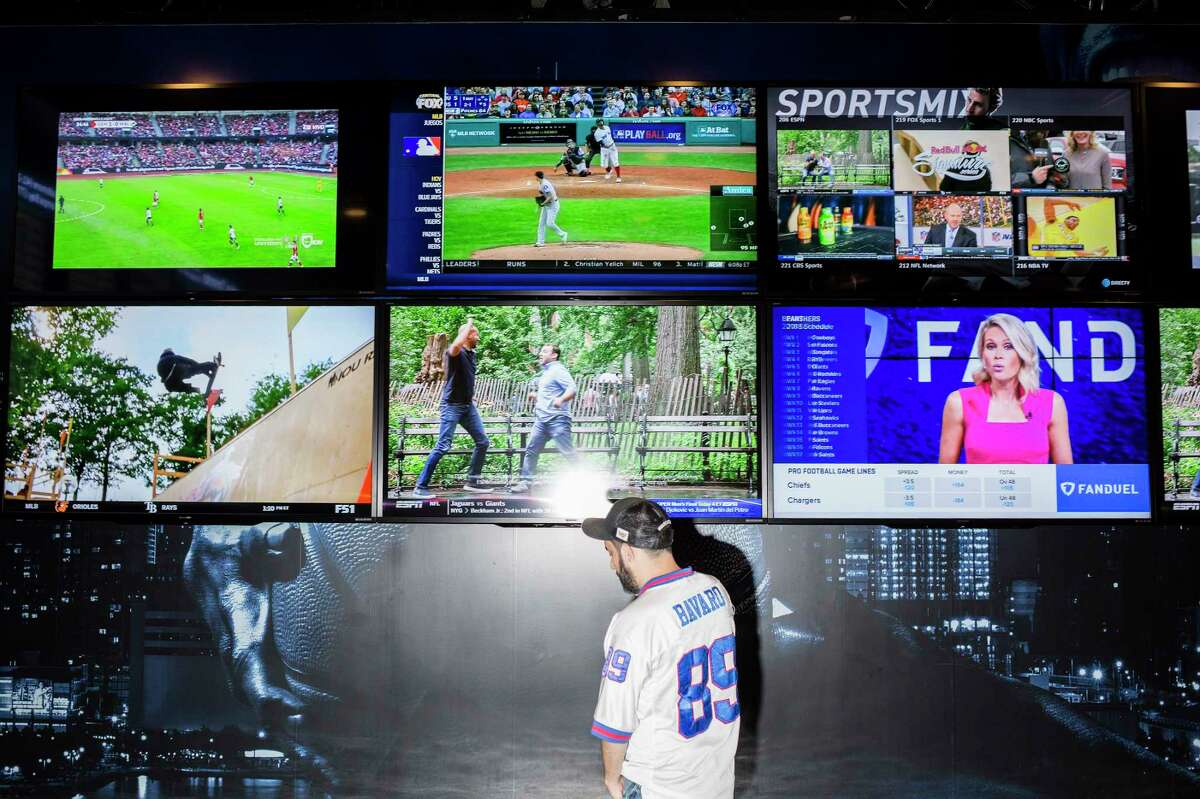 A New York Giants fan in front of television screens at the FanDuel Sportsbook, a legal sports-betting venue, at Meadowlands Racetrack in East Rutherford, N.J., Sept. 9, 2018. The racetrack, which shares a parking lot with MetLife Stadium, the home of the New York Giants, has eagerly been awaiting Week 1 of the NFL season. (Bryan Anselm/The New York Times)