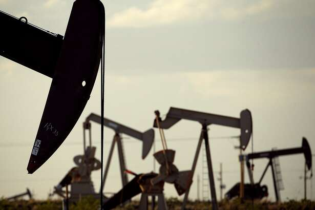 """FILE - In this April 24, 2015 file photo, pumpjacks work in a field near Lovington, N.M. The United States may have reclaimed the title of the world's biggest oil producer sooner than expected. The U.S. Energy Information Administration said Wednesday that America """"likely surpassed"""" Russia in June and August after jumping over Saudi Arabia earlier this year. (AP Photo/Charlie Riedel, File)"""