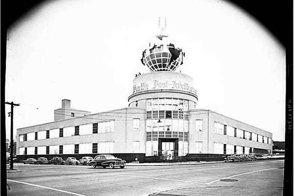 The Seattle Post-Intelligencer building on Wall Street, photographed in 1948. In the late 1940s, the newspaper held a nationwide competition for an architect for a new building on Wall Street. The design included a large, revolving globe with an eagle on top, which stood above the entryway. The streamlined style of the building, with its glass and flat surfaces, was very popular during the 1930s and 1940s. Courtesy of MOHAI