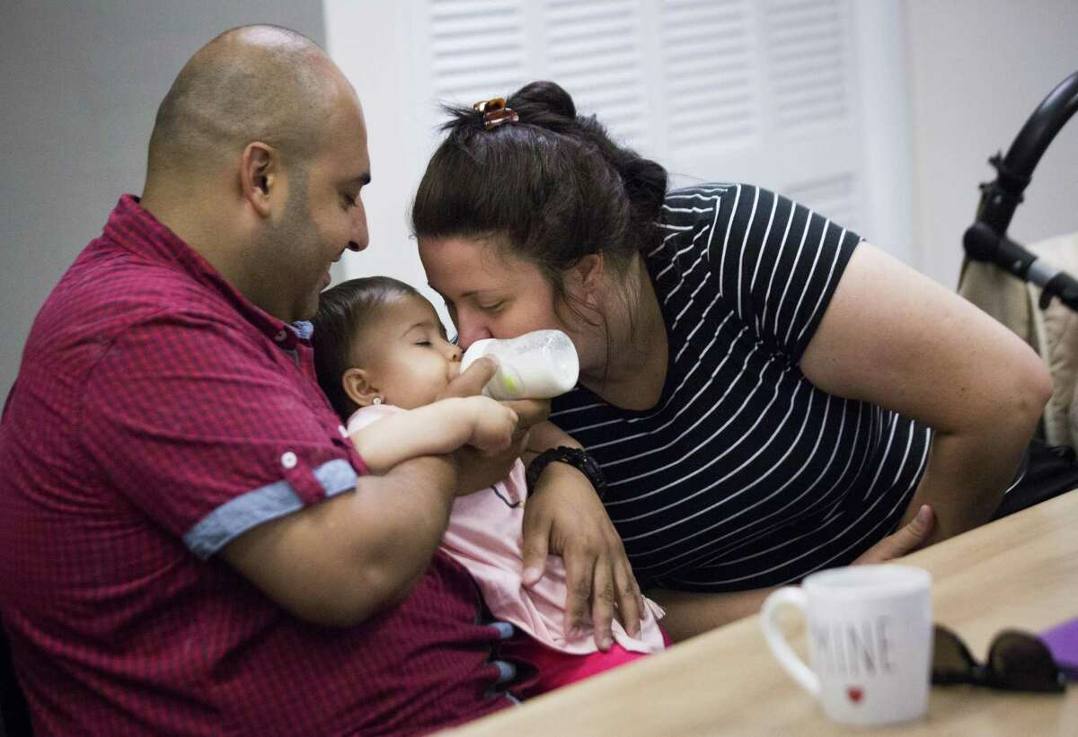 Daniela Dobrescu a native of Romania kisses her daughter Sofia Saeed while her husband Ali Saeed gives milk to the 11-year-old during an orientation class for refugees, Aug. 28 in Houston. The U.S. is setting a low ceiling for refugees generally into the U.S.
