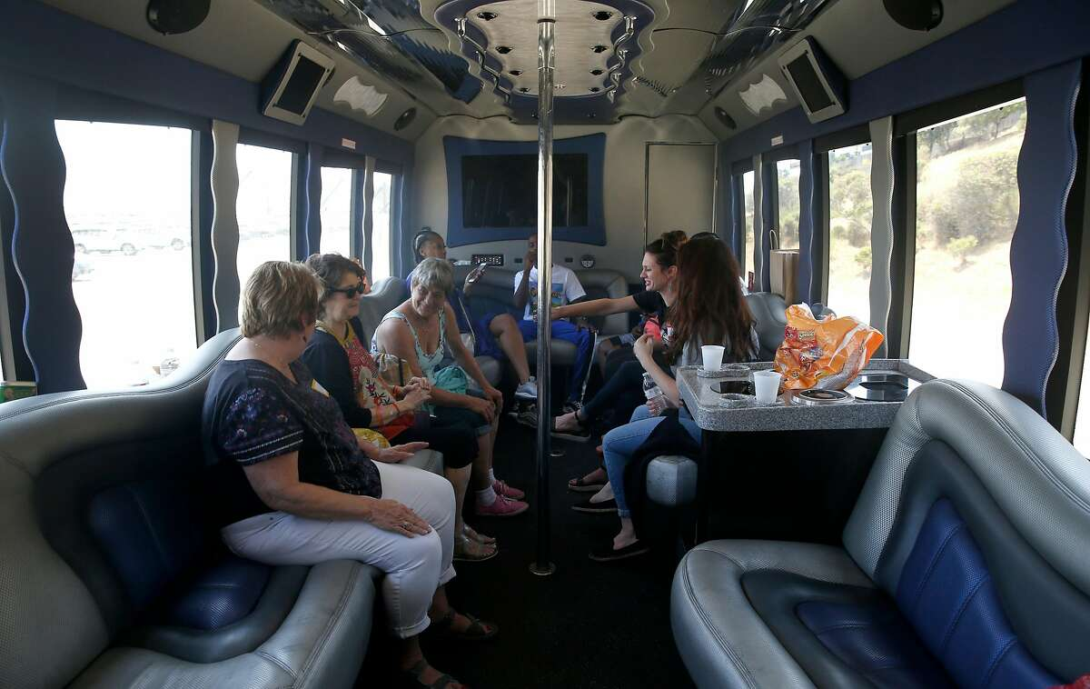 Guests ride aboard a party bus headed for the Urban Legend wine tasting room, the last stop on the Weed and Wine Tour in Oakland, Calif. on Saturday, July 21, 2018.