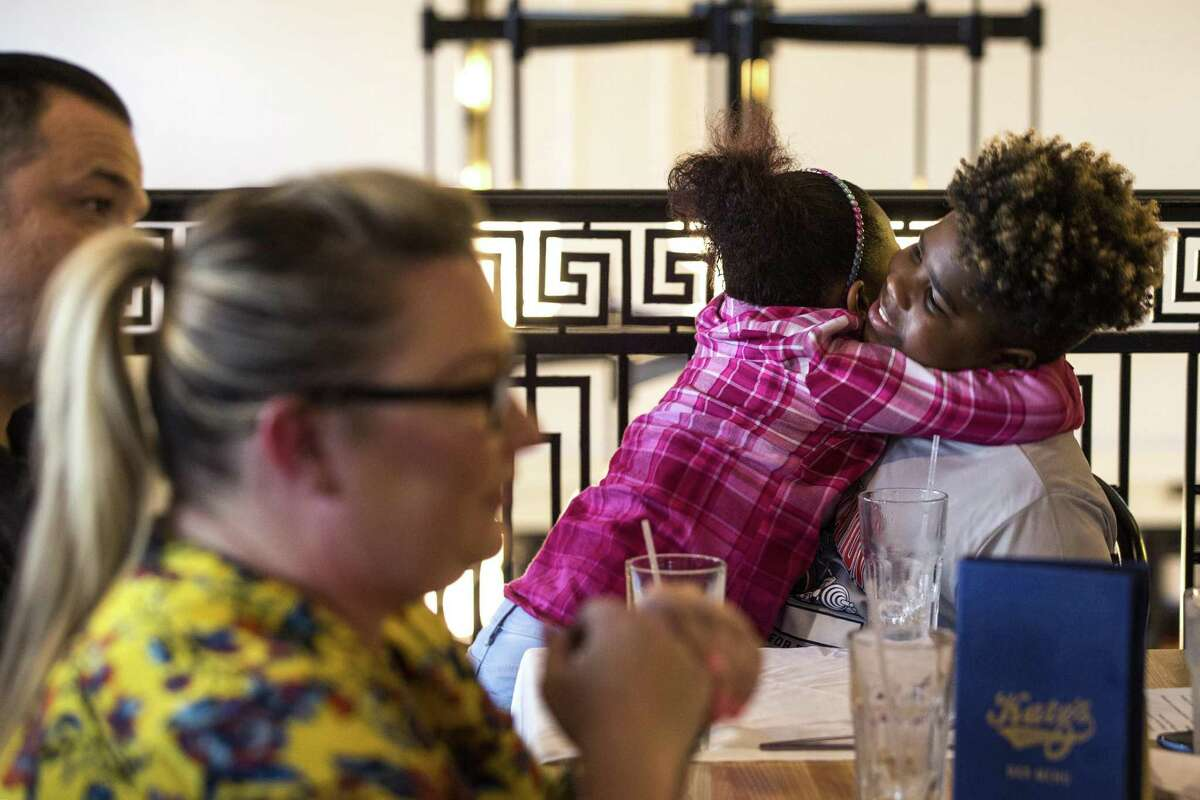 Elease Dibrell, 7, embraces her brother, Noaah Donaldson, 12, as they attend a dinner of the family intervention treatment court alumni group with their mother, Tanja Dibrell, on Friday, Aug. 31, 2018, in Houston.