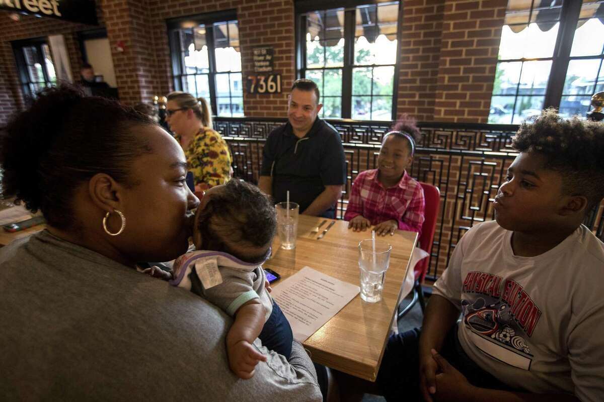 Tanja Dibrell, left, kisses her baby, Jewel, as she attends a dinner the family intervention treatment court alumni group with her son, Noaah Donaldson, 12, and Elease Dibrell, 7, on Friday, Aug. 31, 2018, in Houston.