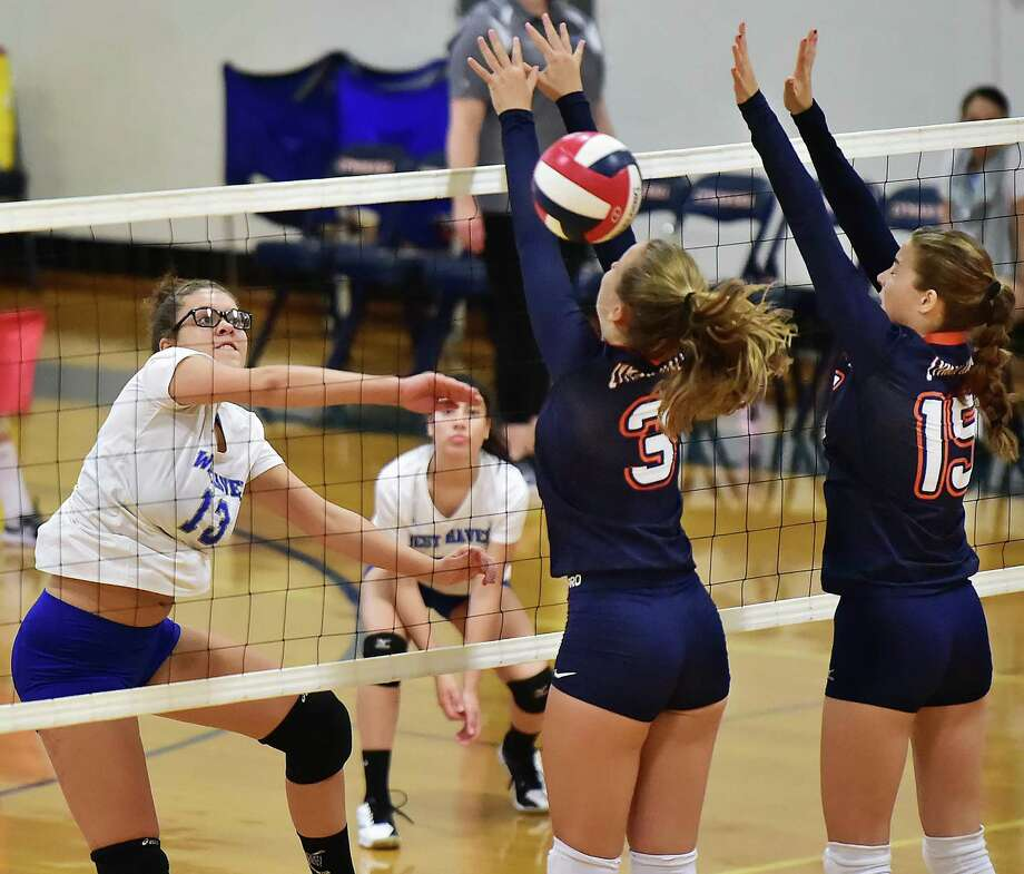 West Haven's Bria Stanley (13) spikes the ball past Lyman Hall's Ellery Campbell (3) and MacKenzie Regan on Wednesday. West Haven won, 3-2 (25-22, 23-25, 25-26, 25-20, 15-13). Photo: Catherine Avalone / Hearst Connecticut Media / New Haven Register