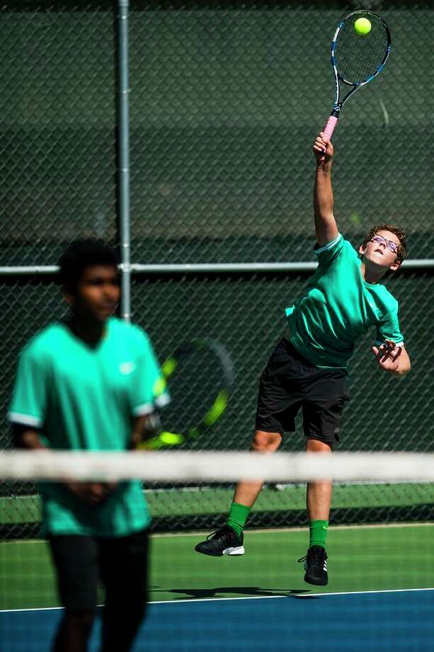Dow sophomore Gavin Killmaster of Dow's #1 doubles pair serves the ball during a match against Forest Hills Central in the Midweek Classic Quad on Wednesday at Greater Midland Tennis Center. (Katy Kildee/kkildee@mdn.net)