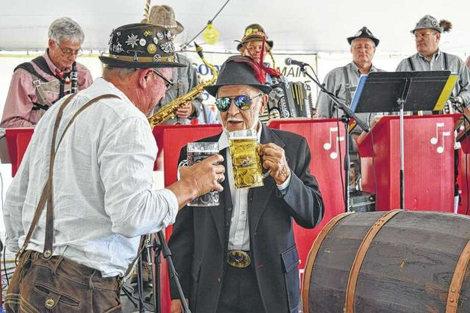 Jacksonville Rotarian Paul Kluge (left) has a beer with his father, Heinz Kluge of Jacksonville, after the elder Kluge tapped the ceremonial keg Sept. 30 at Rotary's 2017 Oktoberfest fundraiser at the Morgan County Fairgrounds. Heinz Kluge is a native of Brandenburg, Germany. Photo: Greg Olson | Journal-Courier