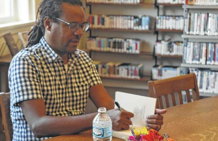"Colson Whitehead signs a copy of his book ""The Underground Railroad"" Wednesday at the Jacksonville Public Library."