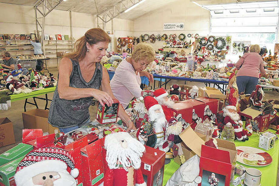 Bonny Biggs Clegg of Springfield (left) and Mary Phalen of rural Jacksonville, members of the Jacksonville Salvation Army Women's Auxiliary, set out holiday decorations Wednesday for the auxiliary's annual Holidays on Parade sale. The sale will be from 8 a.m. to 4 p.m. Friday and 8 a.m. to noon Saturday at the Morgan County Fairgrounds. Photo: Greg Olson | Journal-Courier