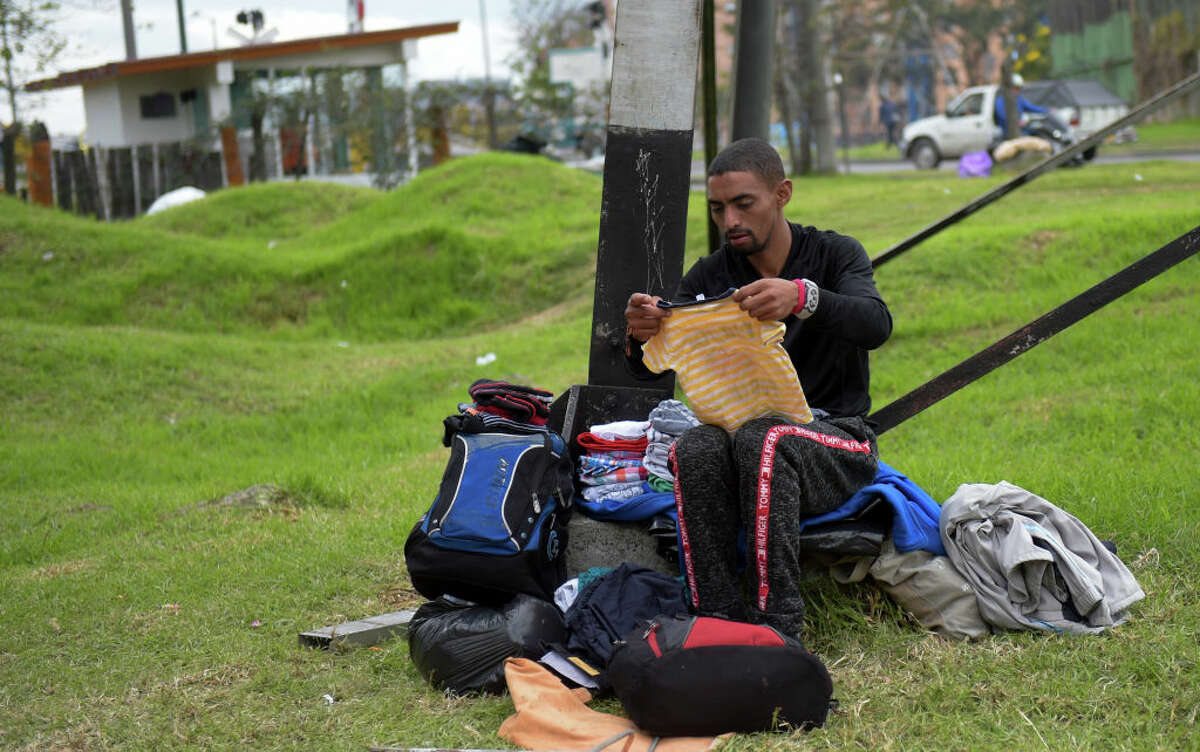 A Venezuelan migrant sorts out donated clothes at an improvised camp near a bus terminal in Bogota on September 11, 2018. More than one hundred migrants set up a makeshift camp in a wooded area, near the bus terminal where they arrived, whether to stay in Colombia or to continue their journey.