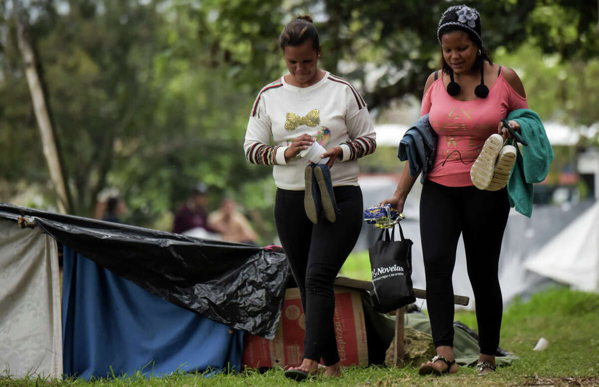 Venezuelan migrants are pictured at an improvised camp near a bus terminal in Bogota on September 11, 2018. - More than one hundred migrants set up a makeshift camp in a wooded area, near the bus terminal where they arrived, whether to stay in Colombia or to continue their journey. (Photo by Raul ARBOLEDA / AFP) (Photo credit should read RAUL ARBOLEDA/AFP/Getty Images)