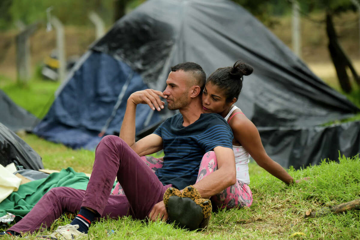 A Venezuelan migrant couple, remains at an improvised camp near the bus terminal in Bogota on September 11, 2018. More than one hundred migrants set up a makeshift camp in a wooded area, near the bus terminal where they arrived, whether to stay in Colombia or to continue their journey.