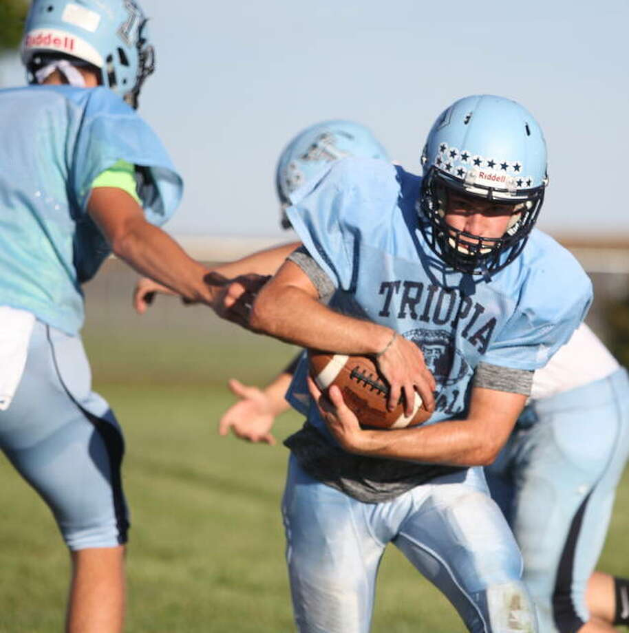The Trojans run a play on offense during practice Wednesday at Triopia. Photo: Dennis Mathes | Journal-Courier