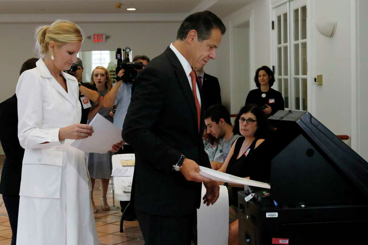 New York Gov. Andrew Cuomo, accompanied by his girlfriend Sandra Lee, puts his primary election ballot in a scanner at the Presbyterian Church of Mount Kisco, in Mt. Kisco, NY, Thursday, Sept. 13, 2018.