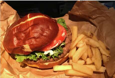 United's original cheeseburger served on a pretzel roll with unusually delicious and crunchy Calbee chips Photo: Chris McGinnis