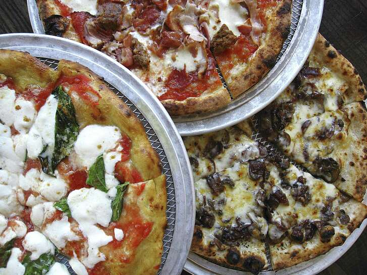 Margherita pizza on a gluten-free rice flour crust, left, a Pork Love pizza and a Fontina pizza with caramelized balsamic onions from Dough Pizzeria Napoletana at Hemisfair.