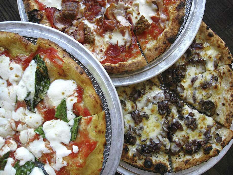 Margherita pizza on a gluten-free rice flour crust, left, a Pork Love pizza and a Fontina pizza with caramelized balsamic onions from Dough Pizzeria Napoletana at Hemisfair Photo: Mike Sutter /Staff File Photo