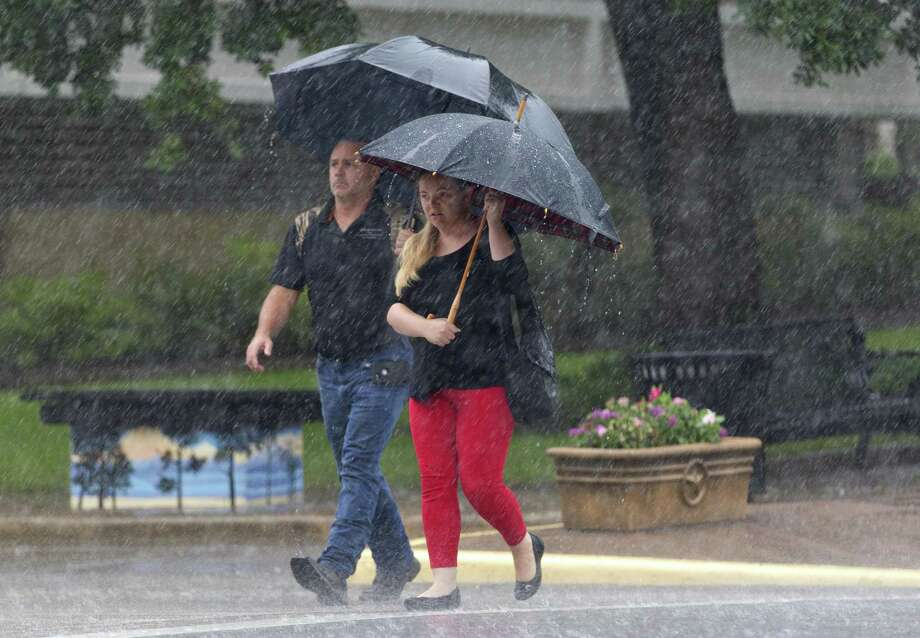 A man and woman make their way through downtown Conroe in heavy rain on Tuesday, July 31, 2018. Photo: Jason Fochtman, Staff Photographer / Staff Photographer / © 2018 Houston Chronicle