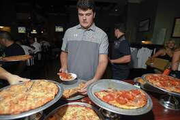 New Canaan resident Jack Conley grabs some slices during the Ruden Report FCIAC Football Media Day at the Colony Grill on Aug. 29 in Norwalk.