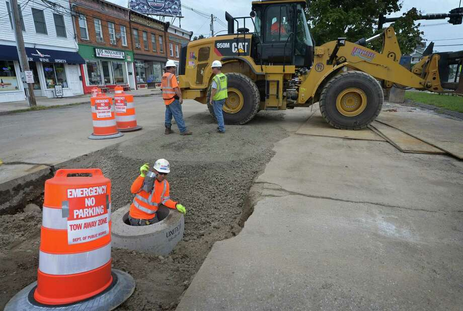 Workers with Middlesex Construction continue drainage work at Liberty Square Wednesday, September 12, 2018, in Norwalk, Conn. After the improvements, the Liberty Square lot will be operated by LAZ Parking Ltd., the company contracted by the parking authority to manage municipal parking in Norwalk. The Parking Management plan includes a combination of transient, monthly and 15-minute parking determined by the Parking Authority. As part of the bridge replacement, the DOT is making the drainage improvements to Goldstein Place and Liberty Square. The approximately $400,000 drainage project began Monday at the southern-most section of Goldstein Place and will continue northward. Photo: Erik Trautmann / Hearst Connecticut Media / Norwalk Hour