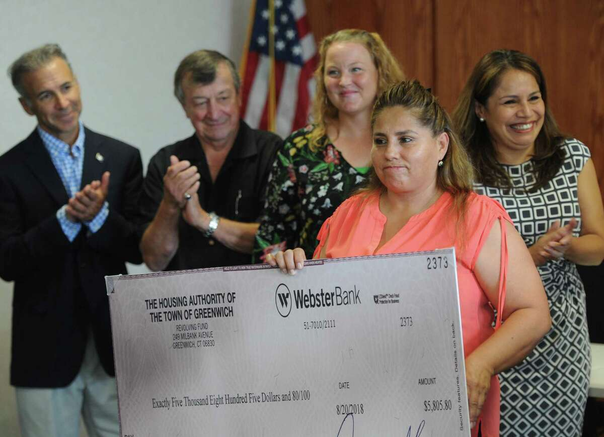 Wilbur Peck public housing resident Narciza Rey accepts a check for $5,805.80 during the Greenwich Housing Authority's Family Self Sufficiency Program check presentation at Town Hall in Greenwich, Conn. Thursday, Sept. 13, 2018. Two Greenwich public housing residents received checks from a special Housing Authority escrow savings account that they've been paying into for the last five years.