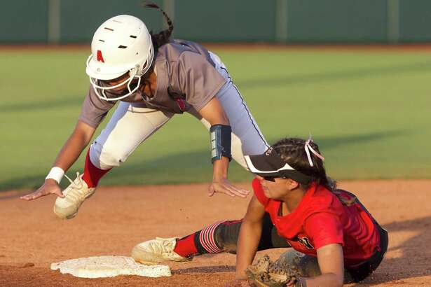 Bryanna Bell #2 of Atascocita flies over Comal Canyon shortstop Sydney Belvin (1) as she steals second base in the sixth inning of the Class 6A state championship game during the UIL State Softball Championships at Red & Charline McCombs Field on Saturday, June 2, 2018, in Austin.