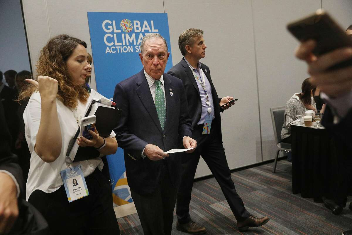 Former New York Mayor Michael Bloomberg (center) walks through Moscone Center South after speaking at a news conference to talk about joint efforts to fight climate change on Thursday, September 13, 2018 in San Francisco, Calif.
