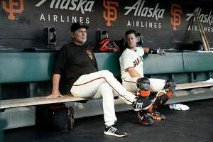 SAN FRANCISCO, CA - AUGUST 31: Manager Bruce Bochy #15 of the San Francisco Giants sits and chats with catcher Buster Posey #28 in the dugout before the game against the St Louis Cardinals at AT&T Park on August 31, 2017 in San Francisco, California. ~~