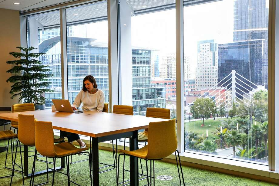 Salesforce employee Emily Stankiewicz works at a communal table on the eighth floor of Salesforce Tower. Photo: Gabrielle Lurie / The Chronicle