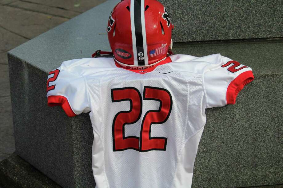 "New Canaan is honoring the late Jason Cooper with his No. 22 jersey and a ""Coop"" sticker on the back of its helmets. Photo: Anthony E. Parelli / Hearst Connecticut Media / Darien News"