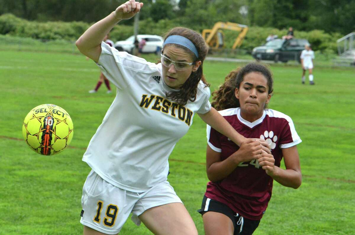 Weston's Katie Orefice, left, brushes off a Bethel defender and gets to the ball during Thursday's game in Bethel.