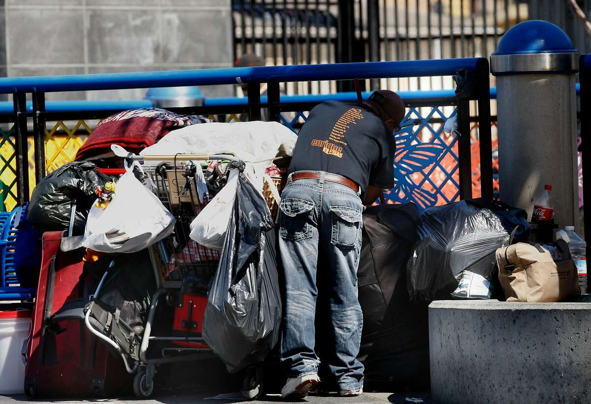 A man going through his belongings on the street level plaza of the Bart station on Mission at 16th streets in San Francisco, Calif., on Wednesday, July 11, 2012.