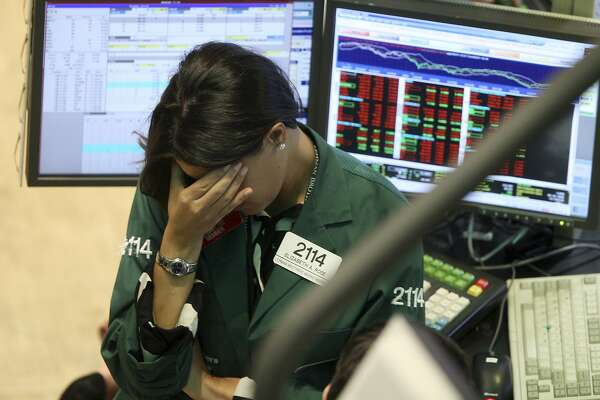 FILE - This Sept. 15, 2008, file photo shows Elizabeth Rose, a specialist with Lehman Brothers MarketMakers, working her post on the trading floor of the New York Stock Exchange. Home prices had sunk, and foreclosure notices began arriving. Layoffs began to spike. Tremors intensified as Lehman Brothers, a titan of Wall Street, slid into bankruptcy on Sept. 15, 2008. The financial crisis touched off the worst recession since the 1930s Great Depression. (AP Photo/David Karp, File)