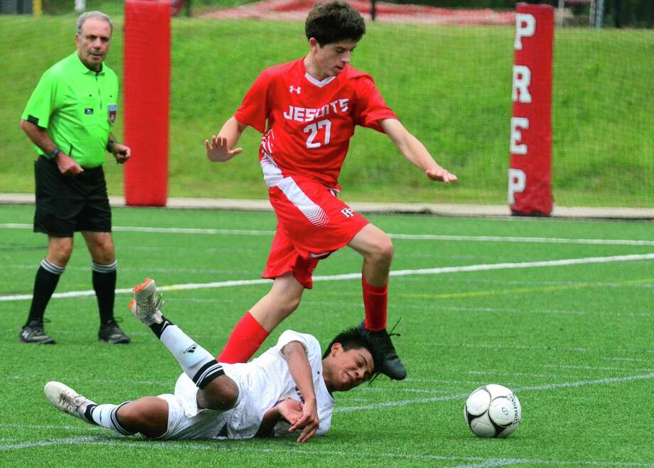 Hillhouse's Cesar Castanon tumbles to the ground as Fairfield Prep's Conner Moore chases the ball over him during Thursday's game in Fairfield. Photo: Christian Abraham / Hearst Connecticut Media / Connecticut Post