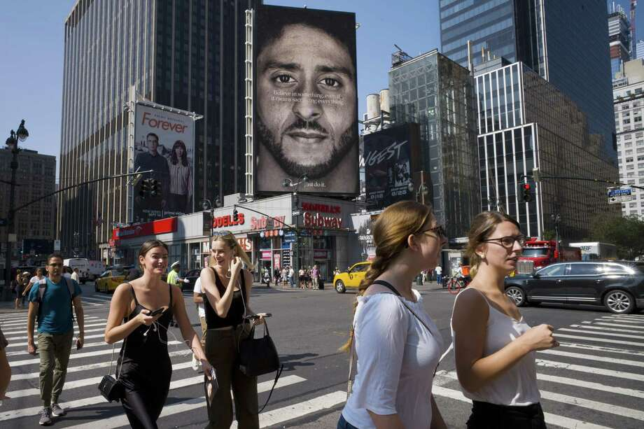 People walk by a Nike advertisement featuring Colin Kaepernick on display Sept. 5 in New York. Photo: Mark Lennihan / Associated Press / Copyright 2018 The Associated Press. All rights reserved.