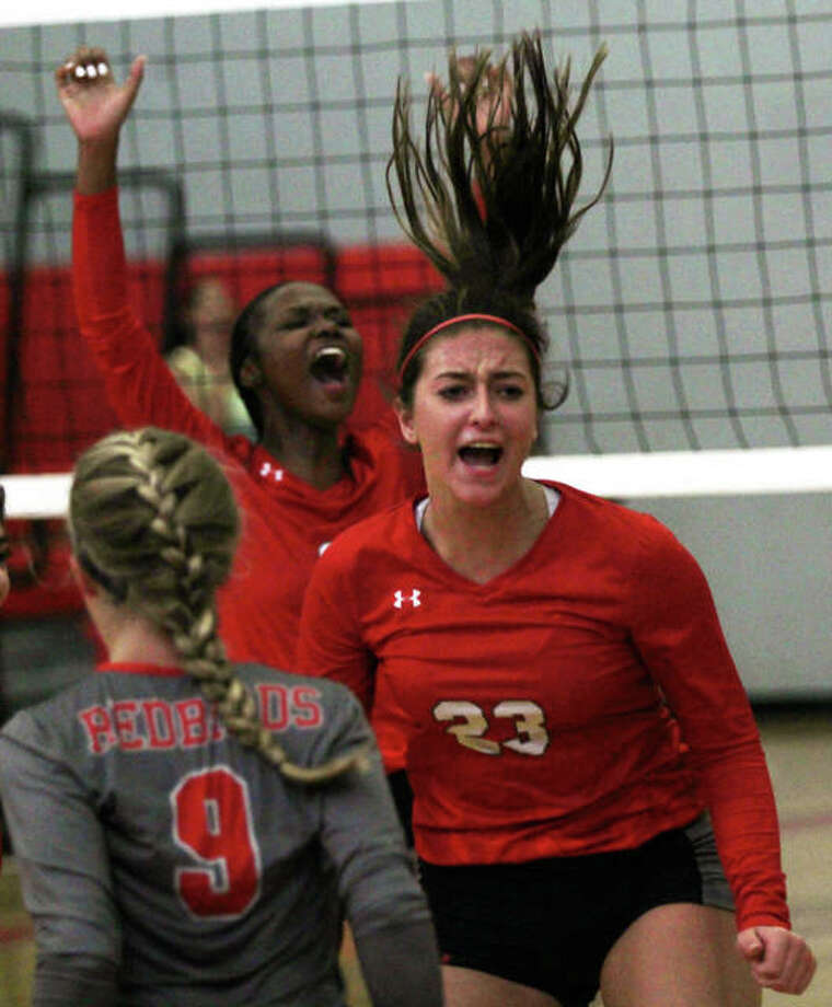 Alton's Abbigail Powers celebrates a point with teammates Leilani Hill (back) and Grace Kane (9) during the second set of the Redbirds' three set SWC victory over East St. Louis on Thursday at Alton High in Godfrey. Photo: Greg Shashack / The Telegraph