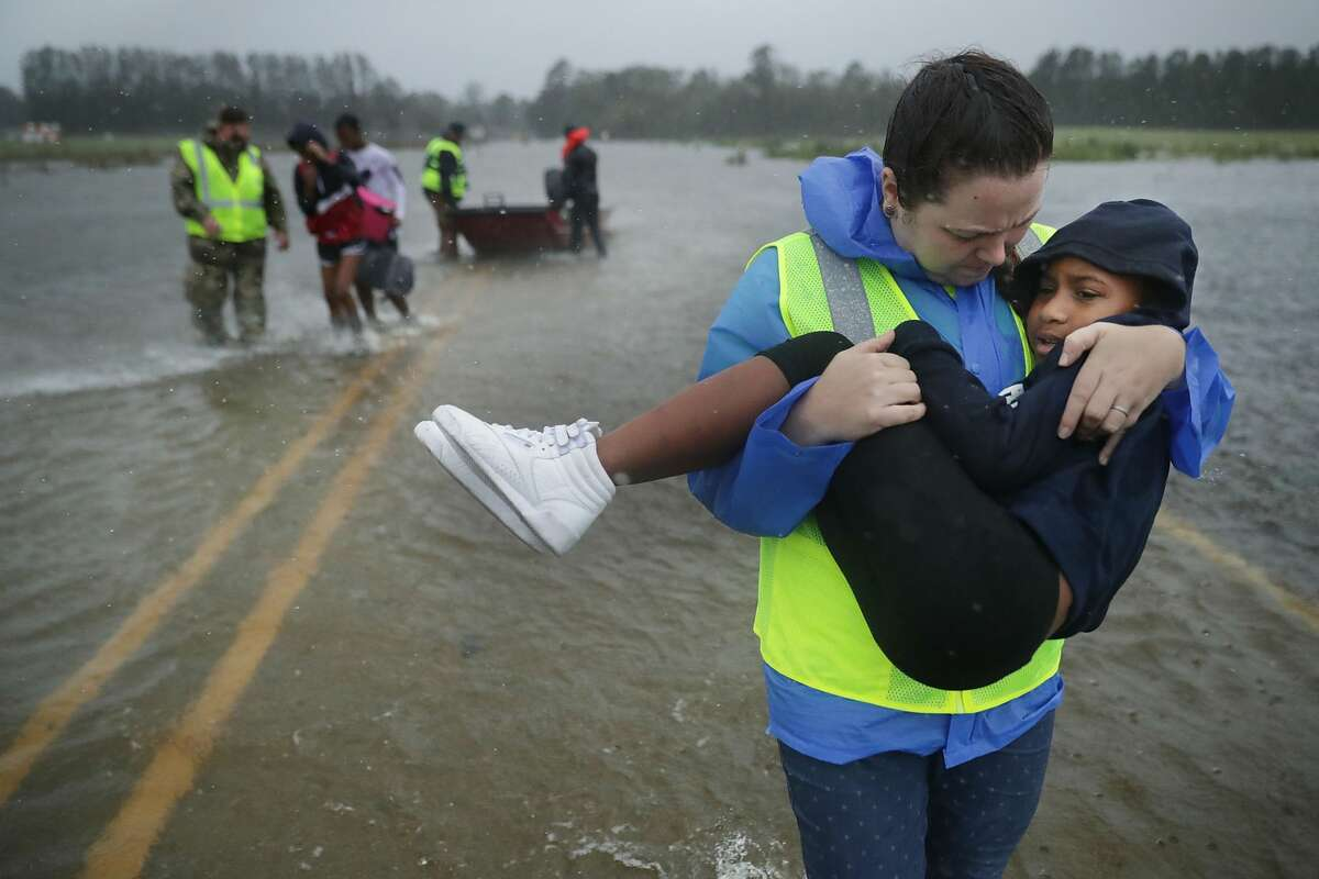 Volunteers from the Civilian Crisis Response Team help rescue three children from their flooded home September 14, 2018 in James City, United States. Hurricane Florence made landfall in North Carolina as a Category 1 storm and flooding from the heavy rain is forcing hundreds of people to call for emergency rescues in the area around New Bern, North Carolina, which sits at the confluence of the Nueces and Trent rivers.