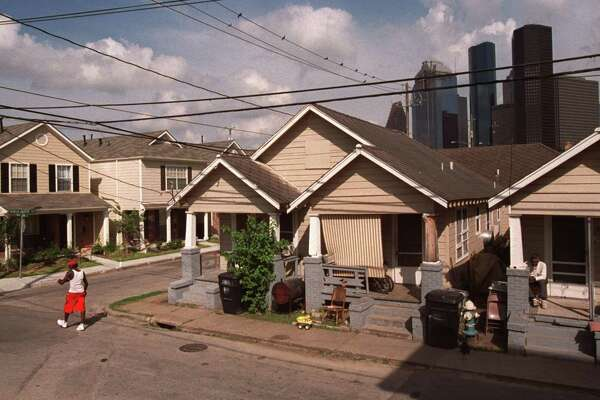 CONTACT FILED: FREEDMEN'S TOWN-HOUSTON Downtown Houston's skyline is seen beyond dilapidated housing along Valentine while brand new homes, on the left are also visible in Houston's 4th Ward. The neighborhood has been unable to fend off the gentrified world of Midtown at its borders, Freedmen's Town in Fourth Ward has its own plan for urban renewal--tear down most of Houston's oldest neighborhood and rebuild it in the same turn-of-the century style. HOUCHRON CAPTION (10/03/2002 - 2-STAR): Houston's skyline forms a backdrop to the aging shotgun houses and new homes in the Fourth Ward. In an effort to fend off the gentrified world of Midtown at its borders, a trio of Baptist ministers has come up with an urban renewal plan for a section of the ward known as Freedmen's Town. HOUCHRON CAPTION (10/03/2002): Houston's skyline forms a backdrop to the aging shotgun houses and new homes in the Fourth Ward. A trio of Baptist ministers has come up with a plan to rebuild a section of the ward known as Freedmen's Town in a way that would preserve the neighborhood's legacy.