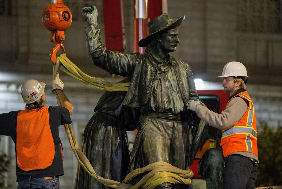 "Workers remove the ""Early Days"" statue from Civic Center Plaza in San Francisco early Friday. Photo: Jessica Christian / The Chronicle"
